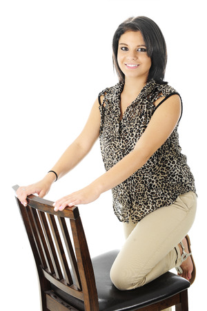 sandles: A happy teen girl with one leg kneeling on a tall chair On a white background. Stock Photo