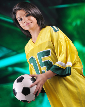 oversized: An attractive teen girl holding a soccer ball while in an oversized yellow and green soccer jersey. Stock Photo