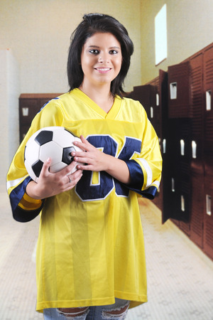 oversized: A beautiful teen girl in an oversized jersey, clutching a soccer ball in a locker room.   Stock Photo