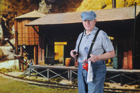 A senior train engineer holding an oil can and rag by an old freight station.   Stockfoto