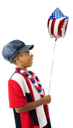 Profile of a young elementary girl wearing red, white and blue, happily looking at the stars and stripes on the balloon she holds.  On a white background. photo