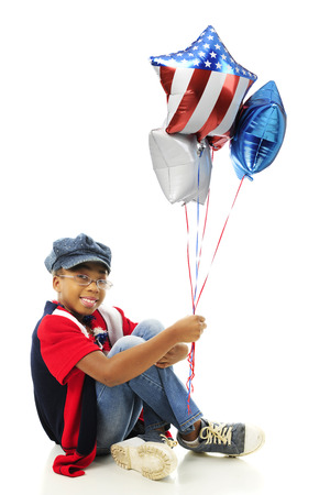 A young elementary African American girl proudly wearing her red, white and blue while holding a small bouquet of heart-shapped balloons.  On a white background. photo