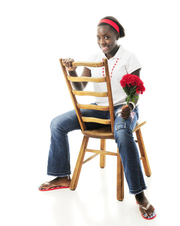 An attractive African American tween sitting backwards on a ladder-back chair while happily holding a bouqet of red flowers.  On a white background. photo