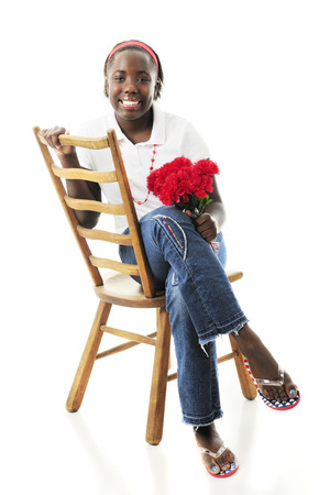 A happy preteen girl sitting pretty in an old ladder-back chair with a small bouquet of red flowers.  On a white background. photo