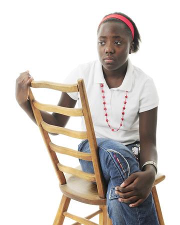 fille triste: Une interpolation fille triste assis sur le c�t� sur une chaise �chelle arri�re. Sur un fond blanc.