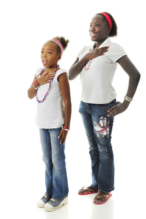 allegiance: Two African American girls standing with hands over their hearts while saying the Pledge of Allegiance.  On a white background.