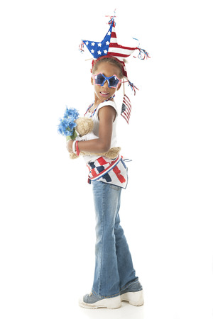 Full-length image of a young elementary girl dressed to display herAmerican  patriotism.  On a white background.