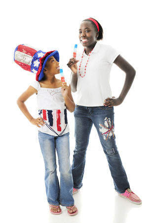 Two sisters  dressed for and celebrating the 4th of July with red, white and blue popcicles.  On a white background. photo