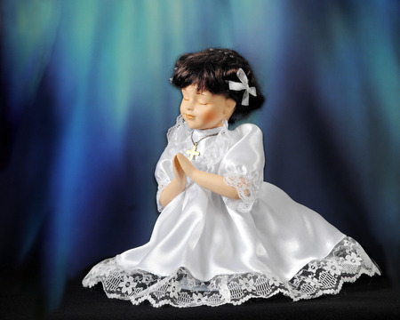 lacey: A praying doll in a communion dress.  Rays of blue light shine down on her.