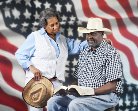 A mature African American cowboy couple reading the Bible with a stars and stripes background. photo