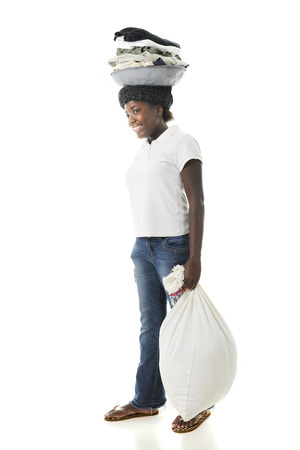 haitian: A Haitian preteen happily hauling laundry on her head while carrying a full back in her hand.  On a white background. Stock Photo