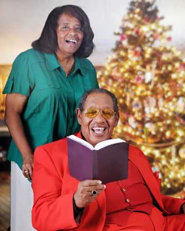 A senior adult couple singing from a songbook in a Christmas decorated living room.