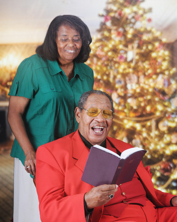 A senior adult man reading scripture in a Christmas-decorated living room.  His wife stands behind looking over his shoulder. photo