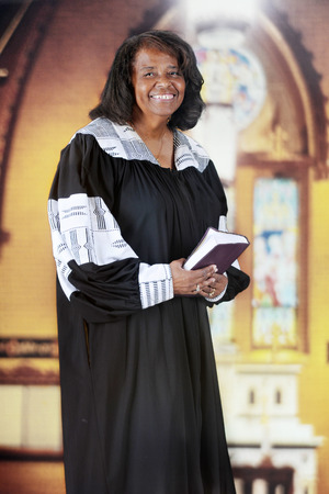 happy african: A  senior-adult woman in her black and white pastoral robe inside an old English Gothic church. Stock Photo