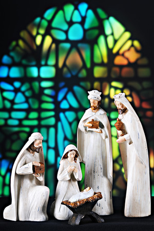 A nativity scene composed of the 3 magi, Mary and the baby Jesus set before a stained glass window. photo