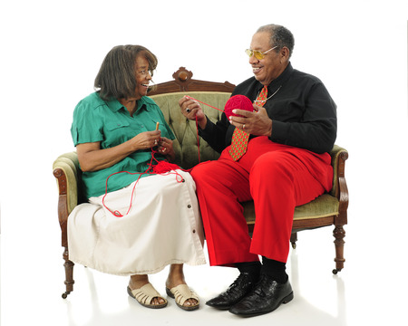 A senior man happily looking at his wife as he hold the yard as she begins a crochet project.  On a white background. photo