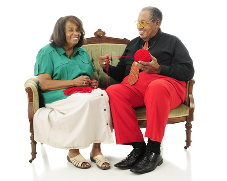 A laughing senior couple sitting on a sofa while she starts a crochet project.  Theyre wearing Christmas colodrs.  Isolated on white photo