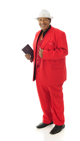 spiffy: Full-length image of a senior man happily holding his Bible while wearing a red 3-piece suit and white fedora.  On a white background.