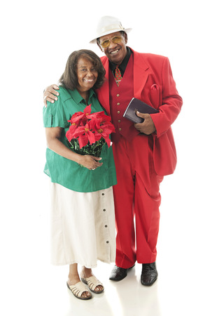 Full-length image of a senior couple dressed for Christmas.  On a white background. photo