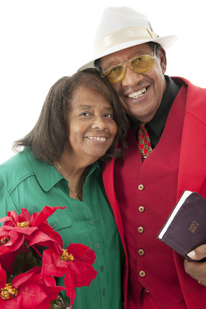 Portrait of a happy senior couple dressed in red, green and white.  She carries a pot of poinsettias.  He carries his Bible.  On a white background. photo