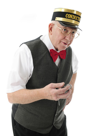 A senior conductor holding his pocket watch while looking for the train.  On a white background. Imagens