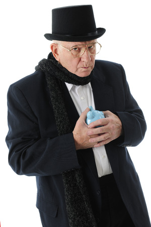 miserly: A miserly Scrouge glaring at the viewer while clutching his piggy bank.  On a white background.