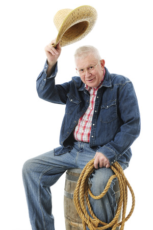 tipping: A senior cowboy tipping his hat in greeting while sitting on an old barrel and with a rope in his hand.  On a white background.