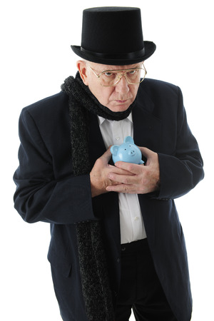 miserly: A grumpy old man in a top hat clinging miserly to his blue piggy bank.  On a white background.