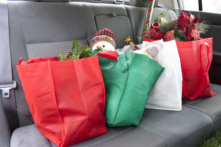 The back seat of a car with four bags of Christmas gifts and decore.