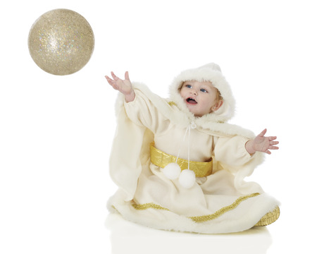An adorable baby Snow Princess happily attempting to catch a sparkly golden sphere.  On a white background.  Motion blur on sphere. photo