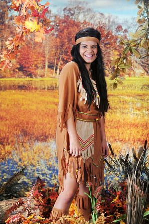 scrunched: An attractive Indian teen scrunched up and laughing as she looks at the viewer from the wetlands.   Stock Photo