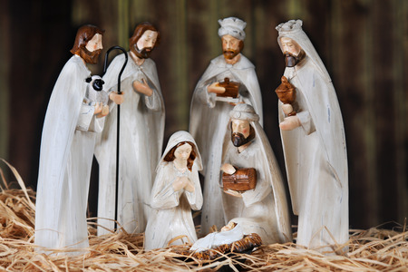 A nativity scene composed of Mary, 3 wise men, 2 Shepards and baby Jesus.  All on a floor of straw in an old wood barn.  Shallow depth of field with focus on Mary.