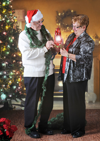 A senior adult couple checking out a Christmas lantern as they decorate their living room for the holidays. photo