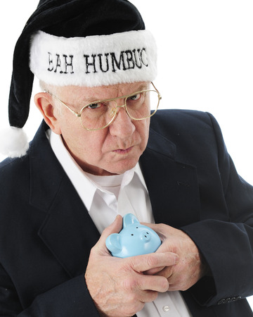 humbug: Close-up image of a grumpy old man clutching his piggy bank and wearing a black Santa hat saying Bah Humbug.  On a white background.