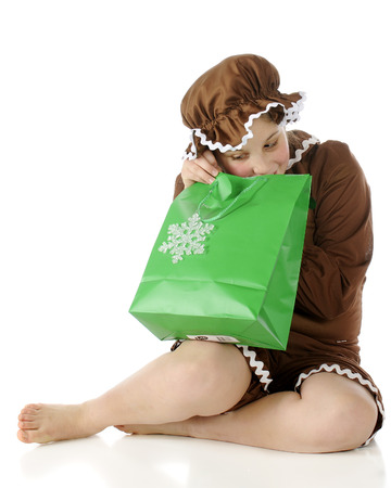 rick rack: A barefoot elementary gingerbread girl peeking into a green Christmas gift-bag.  On a white background.