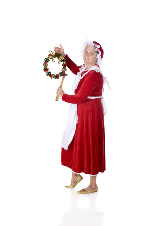 mrs santa: A full length image of Mrs. Santa looking at the viewer as she prepares to hang a jingle bell wreath.  Isolated on white.