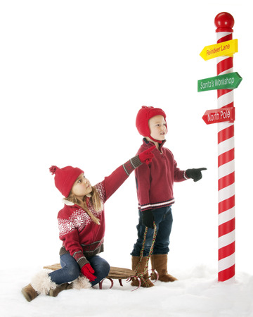 Two young children are on their way to the North Pole.  The sister points the way on one of Santa photo