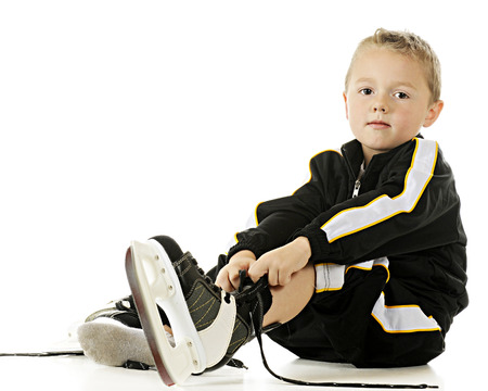 A handsome preschooler in his hockey uniform putting on his skates.  On a white background.  On a white background. Imagens