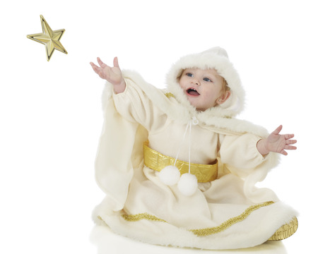 white trim: An adorable baby Snow Princess happily attempting to catch a falling gold star.  On a white background.  Motion blur on star.