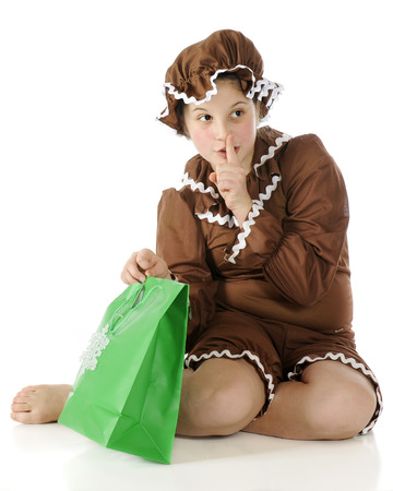 rick rack: A barefoot elementary gingerbread girl gesturing shhhh! while preparing to peek into a green gift bag.  On a white background. Stock Photo