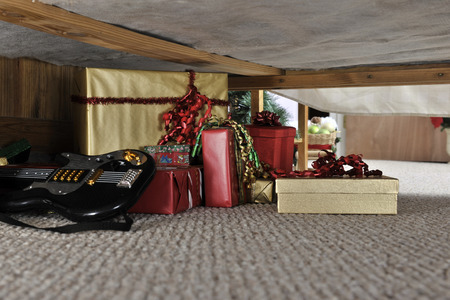 A bunch of wrapped gifts and a toy guitar on a carpet under a bed.