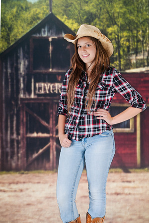 A pretty teen cowgirl standing in front of an old wester livery.
