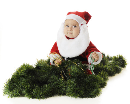 An adorable baby Santa playing with strands of Christmas beads while sitting among green garland.  On a white background.  (Motion blur on hands and beads.) photo