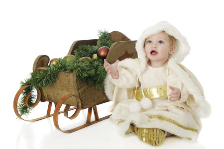 decore: An adorable baby snow princess sitting by a rustic sleigh filled with Christmas decore.  On a white background.