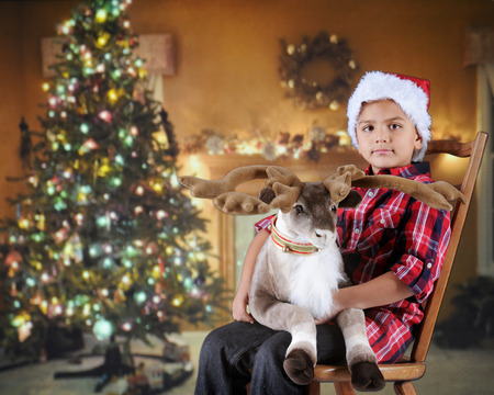 A young elementary boy wishing for Christmas in decorated living room with a reindeer on his lap.