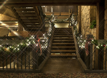 A rustic wooden staircase decorated with Christmas garland, lights and bulbs.
