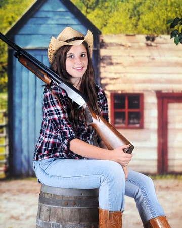 A pretty young cowgirl sitting on a barrel in an old western town.  She carries a rifle propped over her shoulder. photo