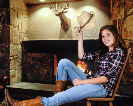 A pretty young teenage cowgirl tipping her hat in greeting as she rests near a fireplace. photo