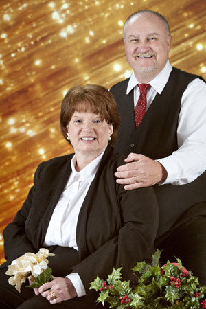 Portrait of a mature couple at Christmastime.  Theyre smiling in front of a bank of diagonal gold lights, with a basket of bright holly in the foreground. photo