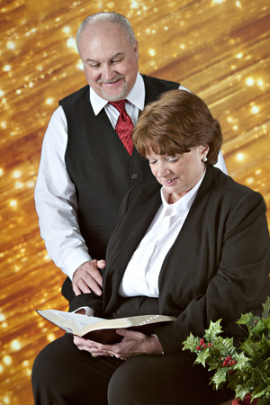 A senior couple reading the Bible together before a bank of diagonal gold lights with holly in the foreground.